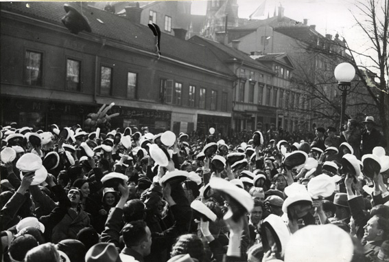 studenter i vita mössor trängs på drottninggatan i uppsala