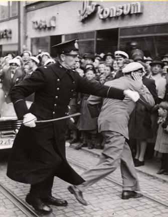 en polis med batong tar fast en student i kavajen