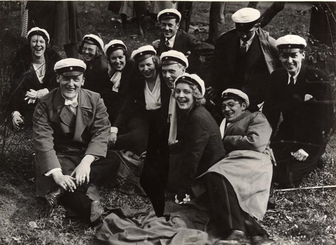 en grupp studenter med vita mössor skrattar och ler in mot kameran