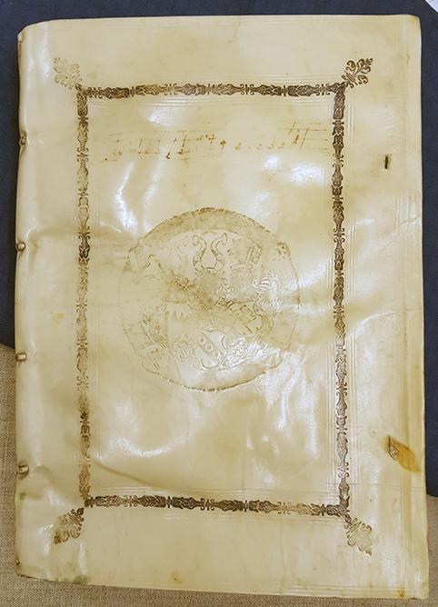 bild på hela främre pärmen, ett vitt pergamentband med ett vapen i guld i mitten