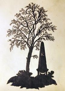 en silhuettklippning av en rest minnessten under ett träd