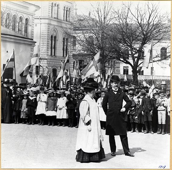 fotografi av selma lagerlöf tillsammans med man i hatt framför en kör av folkskolebarn med flaggor framför universitetshuset