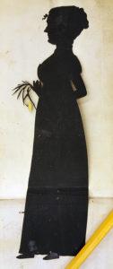 en stående kvinna med en blomma i handen som silhett