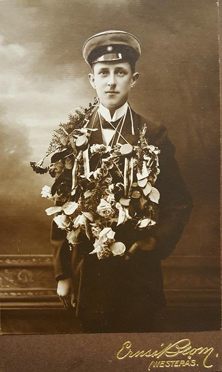 fotografi av student i vit mössa med blommor hängda om halsen