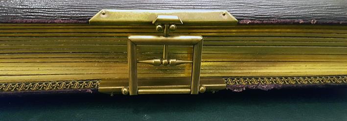 närbild på ett fyrkantigt spänne i guldfärgad metall