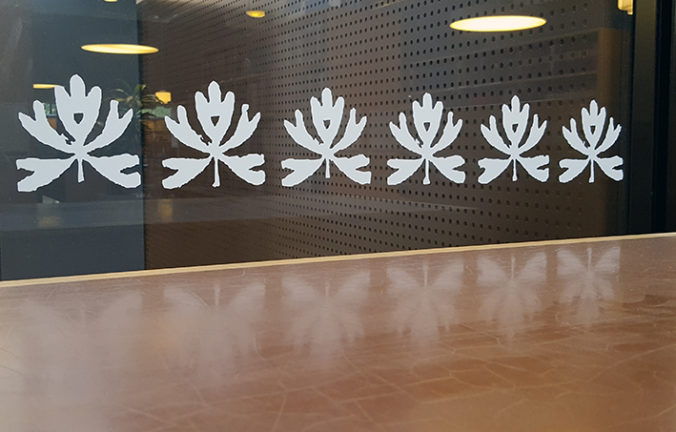 närbild på en rad av bladmönster ingraverade i en glasvägg