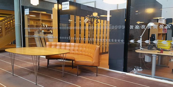 bild på soffa och bord i C-salen, bakom vilken finns en glasvägg med flera olika rader av glasdekor