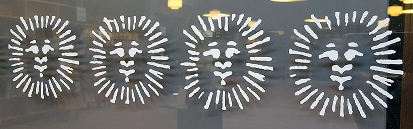 närbild på en rad med graverade solar med ansikten i en glasvägg