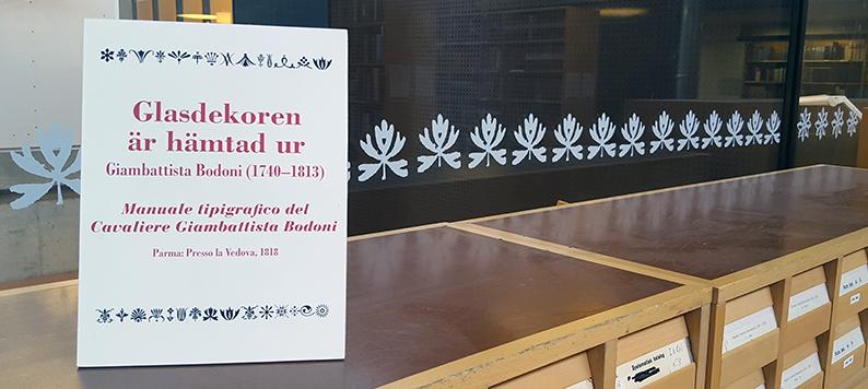 detalj på galsvägg med dekor framför vilken fins en skylt med hänvisning till boken varifrån mönstret är hämtat