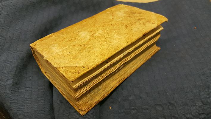 ett slitet ljusbrunt bokband med slitna boksnitt och kanter
