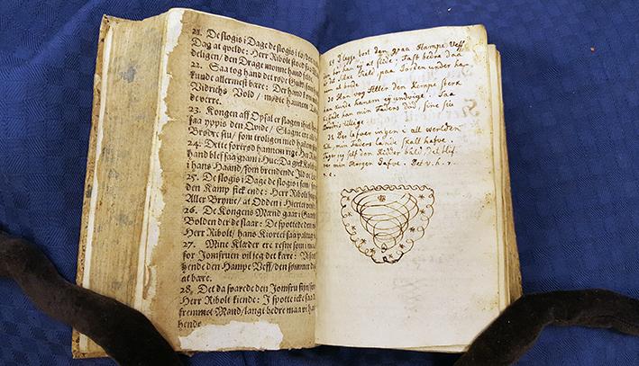 ett uppslag där vänstra sidan är tryckt, högra handskriven med avslutande krumelur under texten