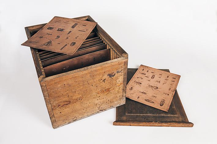 foto på en trälåda med kopparplåtar på högkant, två kopparplåtar ligger framme