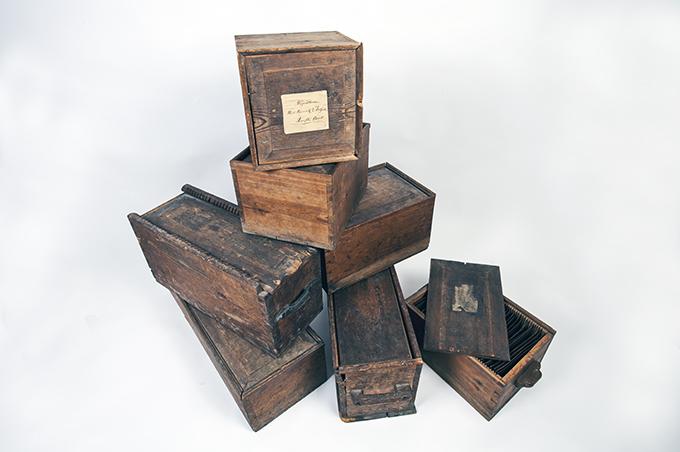 sju trälådor med kopparplåtar stående på varandra