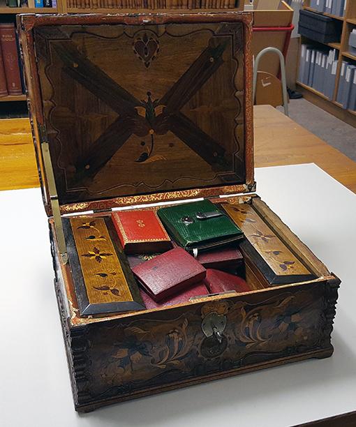 foto på skrinet med öppet lock, och man ser att i skrinet ligger en mängd små fodral i olika färger