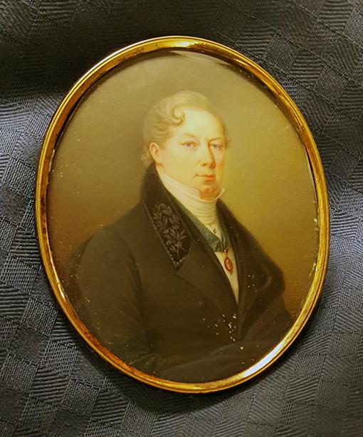 ett porträtt av en man i rund guldram