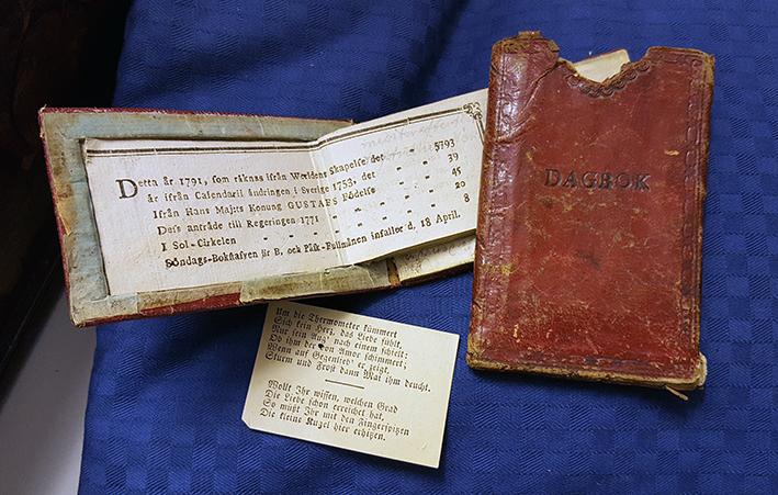 en upplagen almanacka vid sidan av sitt röda läderfodral samt en tysk urklippt tidningsnotis
