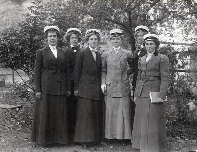 ett svartvitt foto på sex unga damer i studentmössor och hellånga dräkter i en trädgård