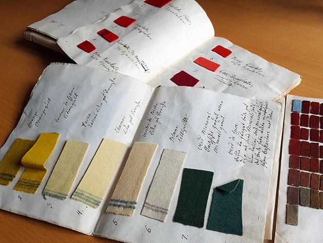tre uppslagna pappersark med fastlimmade tygprover i olika färger