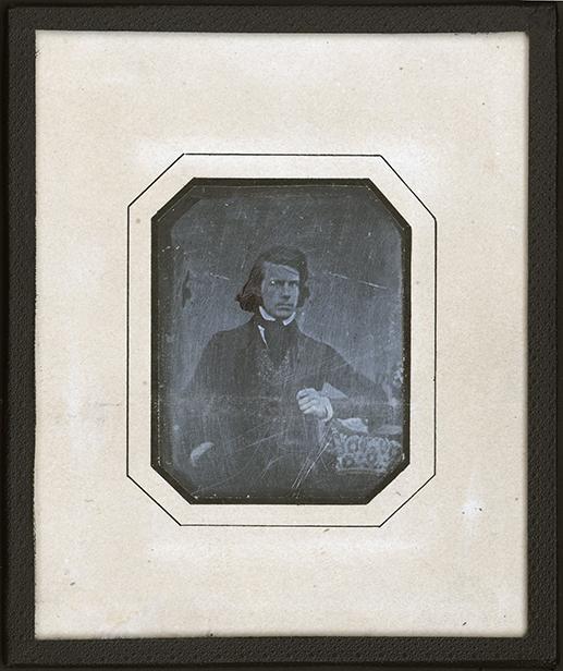 en gråsuddig bild av en man i stärkkrage, kravatt och nästan axellångt hår i sidbena, inom en svart ram