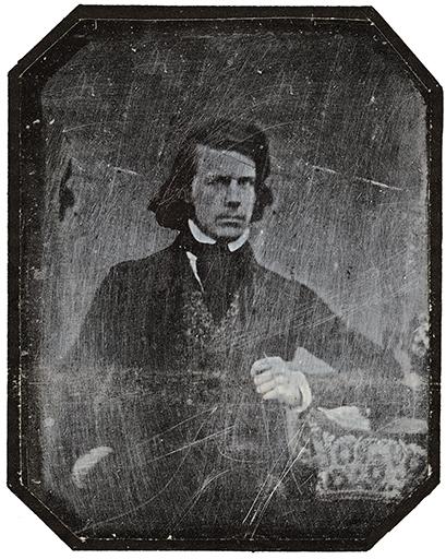 ett gråsuddigt porträtt av en man med stärkkrage, kravaett och nästan axellångt hår i sidbena
