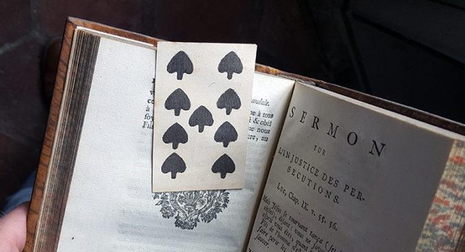 foto av ett spelkort mellan bladen på en bok på franska