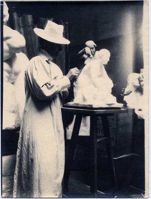 Matton stående iförd dammrock och hatt skulpterar fram en kvinnofigur