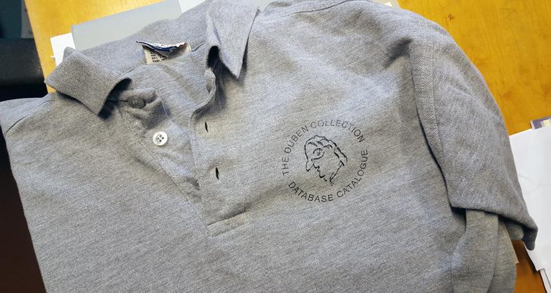 detalj från grå tröja med ansiktet tryckt som logga