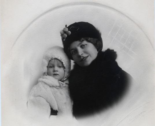 ett svartvitt foto av en kvinna med svart päls och plsmössa med ett barn i vit päls och vit pälsmössa