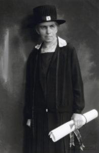 Ida Norrby iförd doktorshatt hållande sitt doktorsdiplom