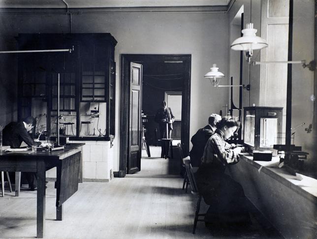 en kvinna och två män arbetar i en laboratoriemiljö