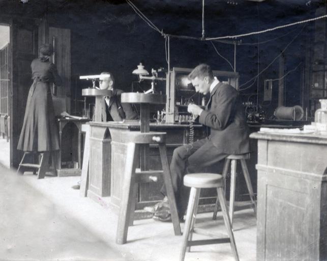 en kvinna läser av en barometer på en vägg och två män arbetar med var sin maskin