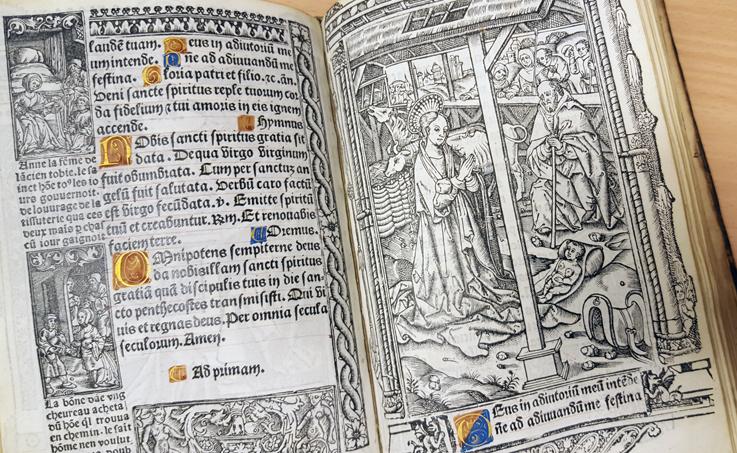 uppslag med krubbscenen och tryckt text med initialer i rött och blått