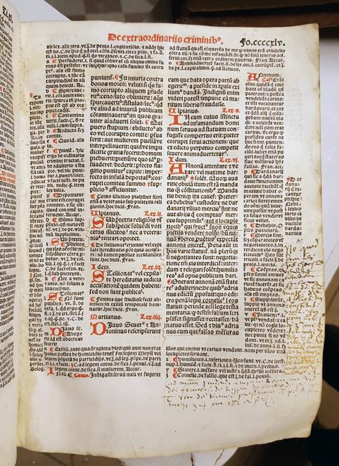 en sida ur boken, dr en text i ett mittfält omges av text runt om. Initialerna är tryckta i rött, övrig text i svart.