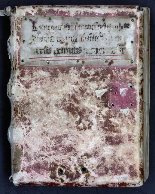 bok bunden i röd pergament, nederst två stora hål där det förut suttit en kedja
