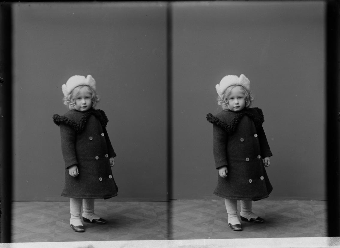 svartvit bild på en liten pojke iförd vit mössa och svart duffel
