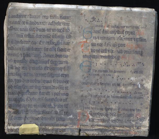 bild på främre pärmen, en smutsad medeltida handskrift med bokstäver i svart, blått och rött