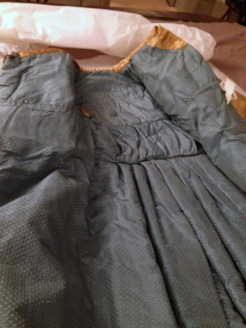 foto på en kappa på ett bord, upplagd så att det blå sidenfodretsyns