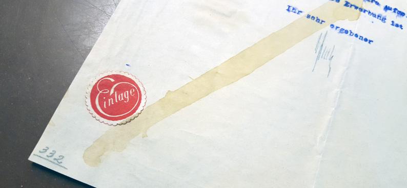 närbild på ett hörn av brevet där randen över pappret syns särskilt tydligt, och där det sitter en liten röd etikett med texten Einlage