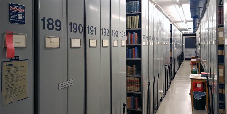 bild på en lång rad med kompaktushyllor, och man ser i en glipa att de är fyllda med böcker