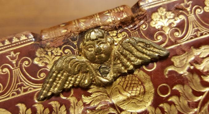 ett bokbandsbeslag i form av ett änglahuvud med vingar i mässing