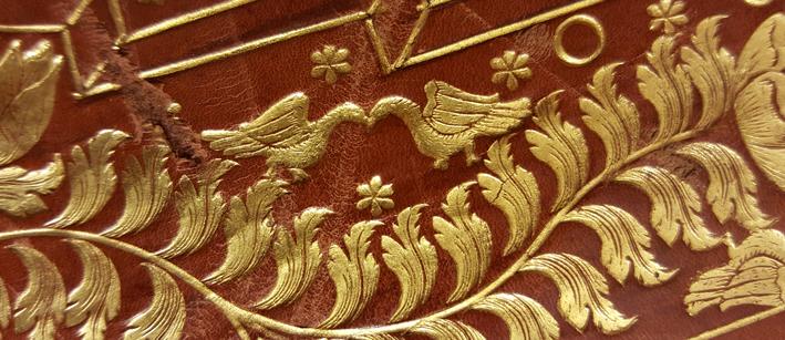detalj av guldtryckt dekor i form av ett par små fåglar med näbbarna mot varandra