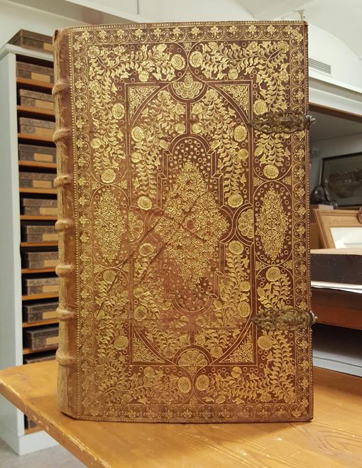 bild på hela framsidan av bokbandet, ett brunt skinnband översållat med guldstämplar i form av blommor, stjärnor, fåglar och annan ornamentik