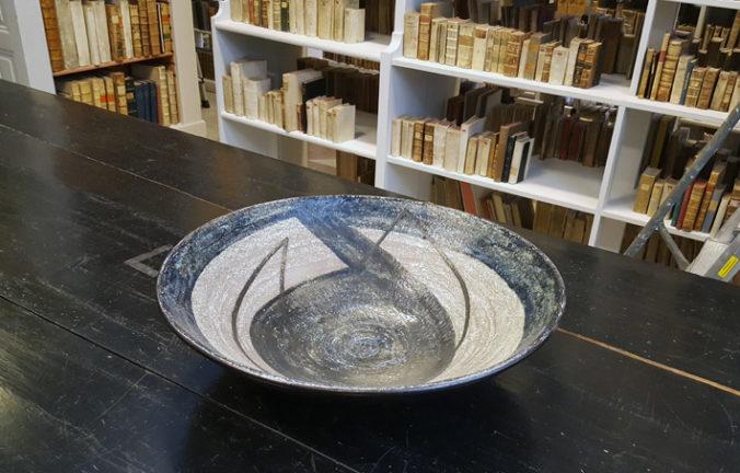 foto på ett keramikfat i ljusgrått och mörkgrått på ett svart bord mitt i ett bokmagasin