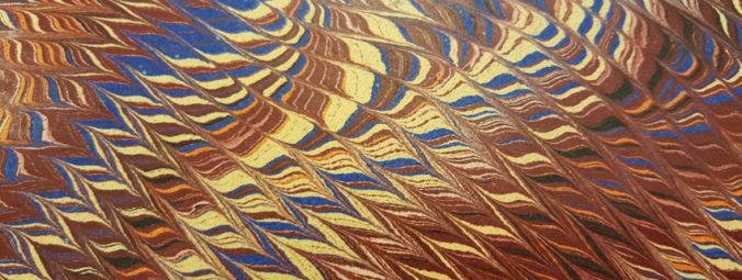 närbild på marmorerat papper i gult, blått, vinrött och orange
