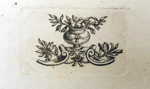 en liten graverad vas med växtslingror