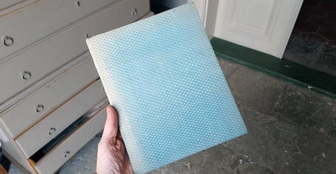 utsidan på pärmen, klädd i ljusblått tyg med upphöjda prickar på. I bakgrunden en grå byrå och ett stengolv