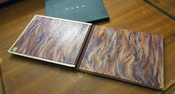 boken ligger uppslagen på ett brunt träbord, så att de första två sidornas marmorering i zickzackmönster syns