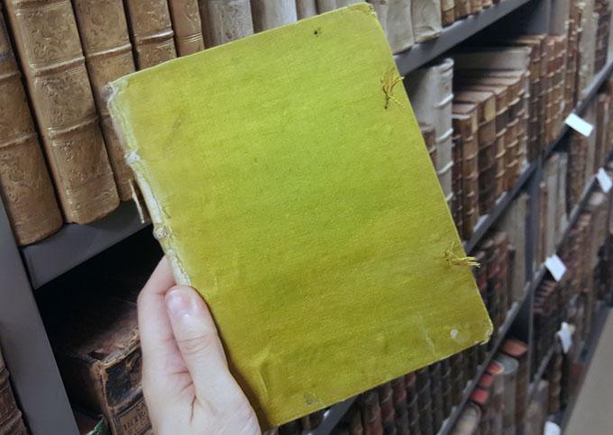 en bok klädd i ärtgrönt tyg hålls upp av en hand framför en bokhylla med gamla böcker