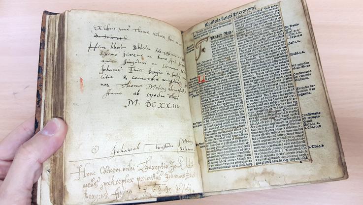 uppslag i boken med tryckt text på högra sidan och handskrivna noteringar på den vänstra