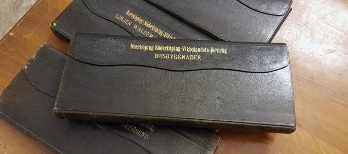 bruna mappar med guldtext på